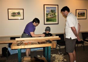 Sally Fishburn Teaching Sam Kenyon How to Use a Bench Plane while Sam's Dad Kyle Watches
